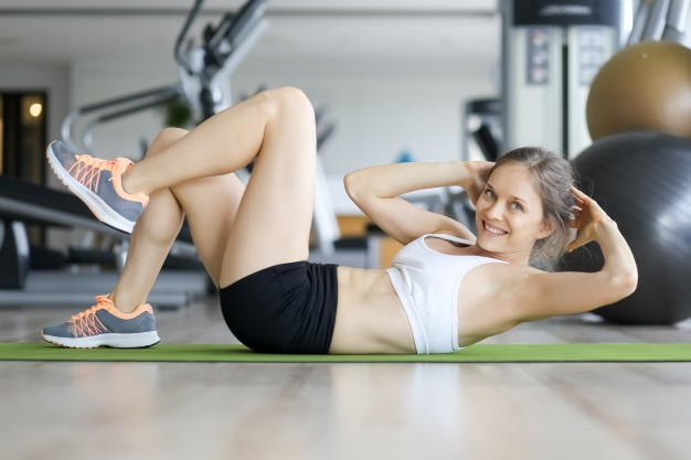 happy young woman doing crunches on mat in gym 1262 3562
