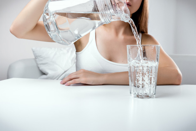 close up of young girl pouring fresh pure water from pitcher into a glass 447 19327000
