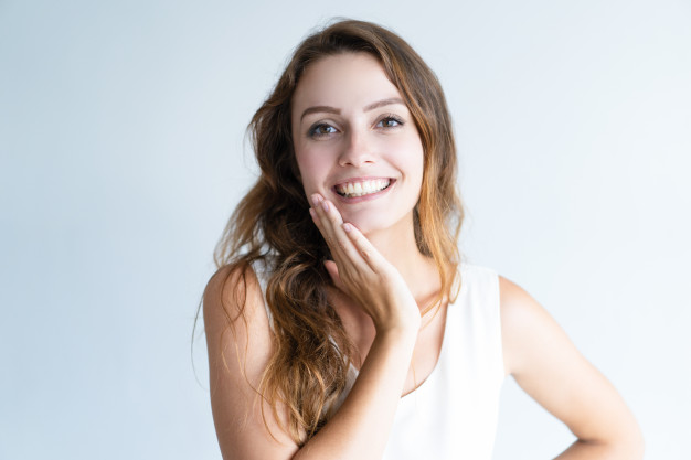 smiling young lovely woman looking at camera and touching face 1262 15247